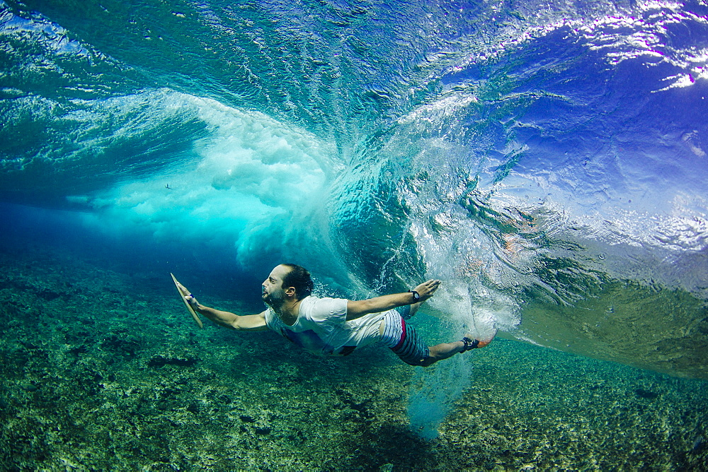 Professional surfer, Indar Unanue, duck dives underneath a wave during a bodysurf session in the South Atolls (Maldives)