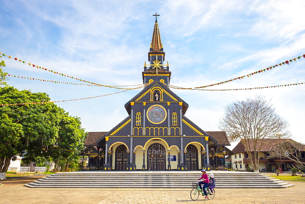 Childen ride a biycycle in front of Kon Tum Cathedral, also known as Wooden Church, Kon Tum, Kon Tum Province, Vietnam