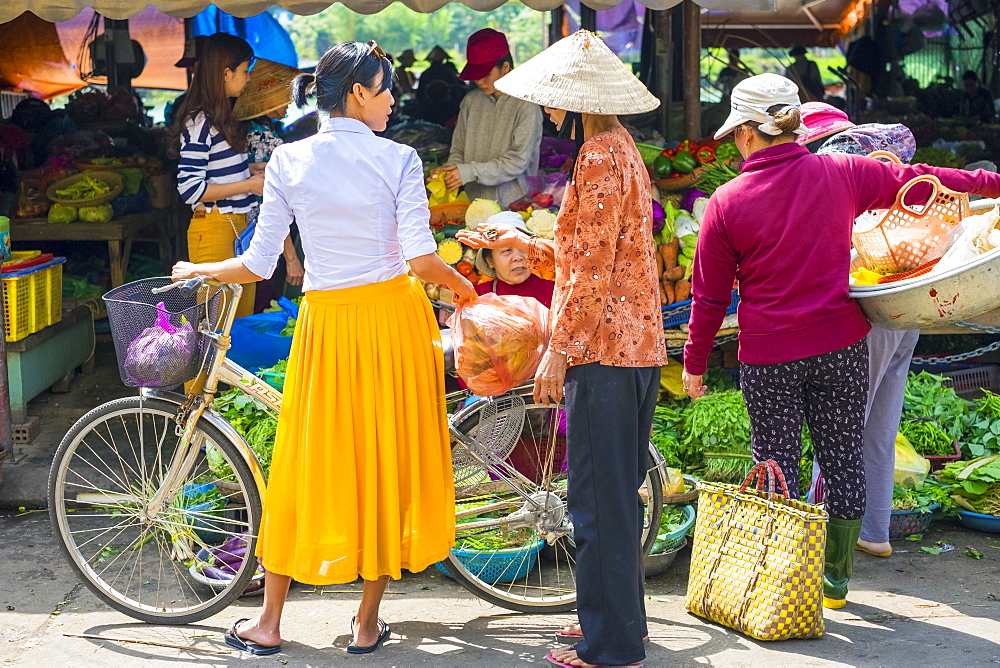 Young Vietnamese woman with bicycle shopping at street market in Hoi An, Quang Nam Province, Vietnam