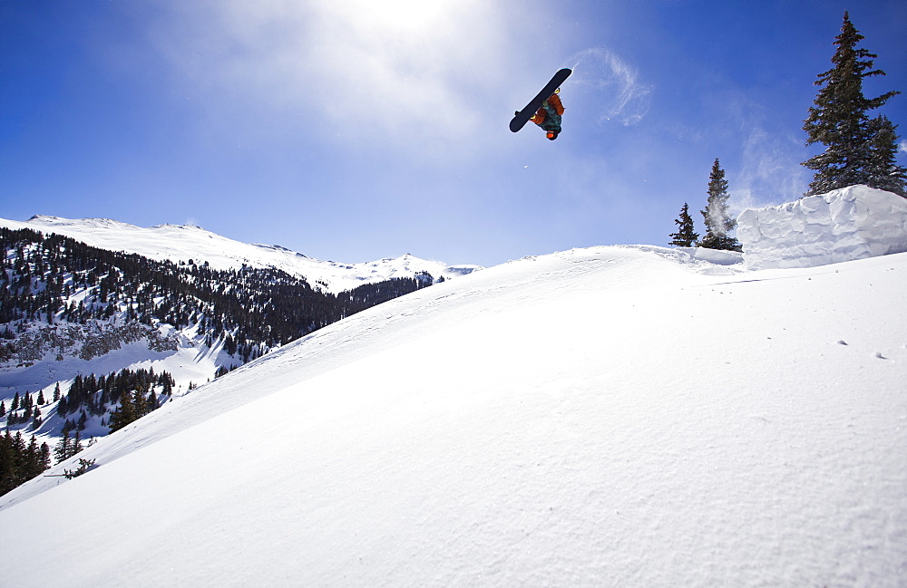 A man hits a backcountry jump on his snowboard on Red Mountain Pass in Southwest Colorado.