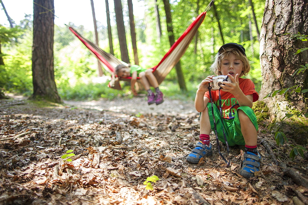 A 5 years old girl in an hammock, with her brother playing with a camera. In a forest, France.