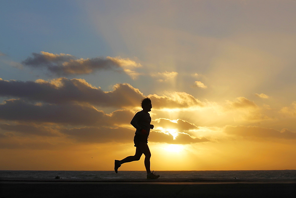 A person jogs as the sun sets at Windansea Beach in the La Jolla neighborhood of San Diego, California.