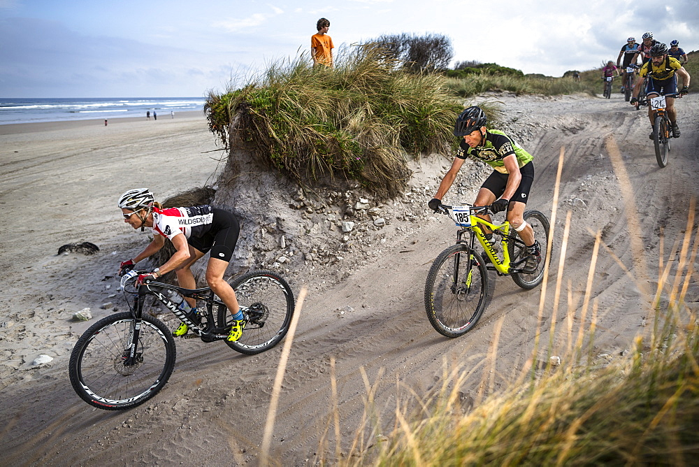 Mountain bikers merge onto Ocean Beach during the last stage of Wildside MTB 2016 in Tasmania.