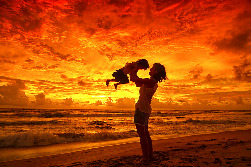 Mother and baby watching sunset on beach, near Unawatuna; Thalpe, Sri Lanka