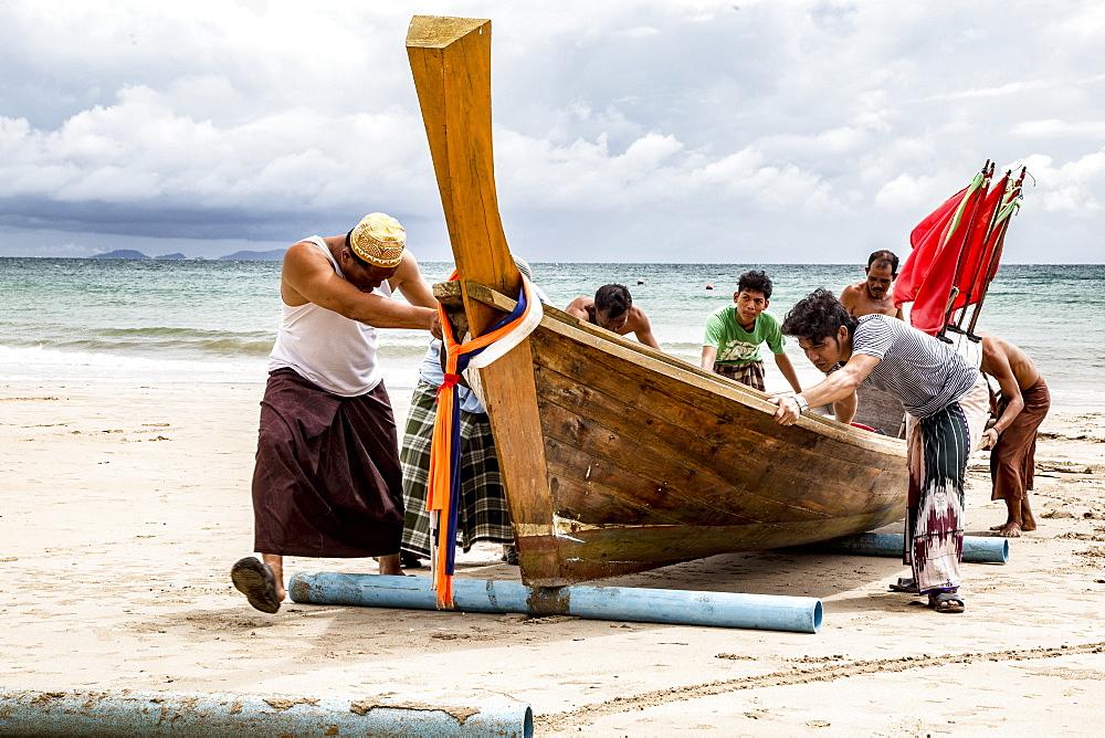 Fishermen on Koh Lanta Island in Thailand push Boat to Shore - 857-92825