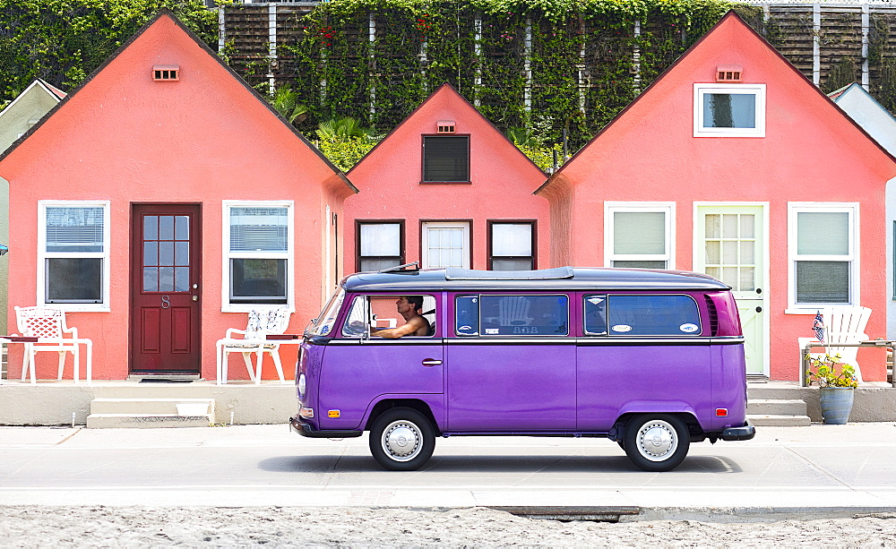 A man drives a purple Volkswagen van down a road in front of a row of pink houses in Oceanside, Calif., on Aug. 3, 2014.