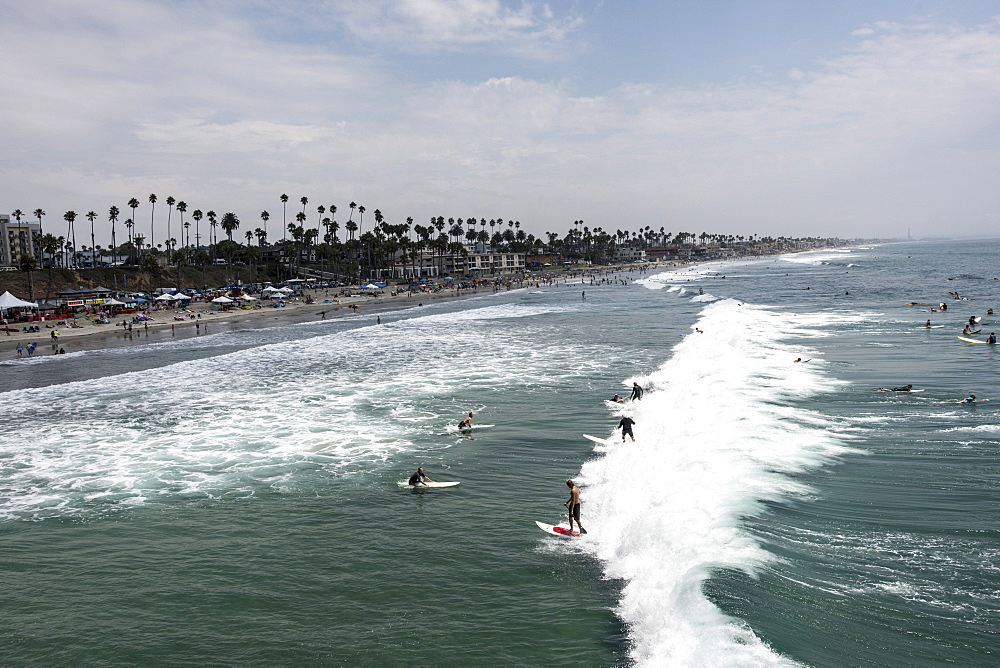"Surfers catch a ""party wave"" after taking part in a paddle out honoring local surfing legend known as Skydog at Oceanside Beach in Oceanside, Calif., on August 3, 2014."