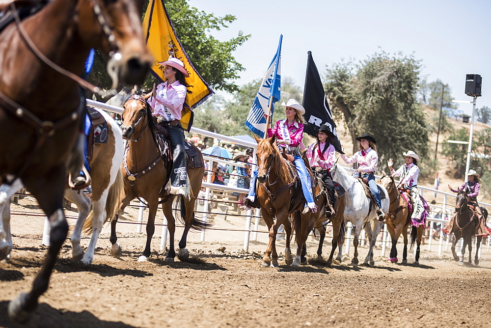 Cowgirls ride their horses during proceedings at the Woodlake Lions Rodeo rodeo in Woodlake, Calif., on May 10, 2015.