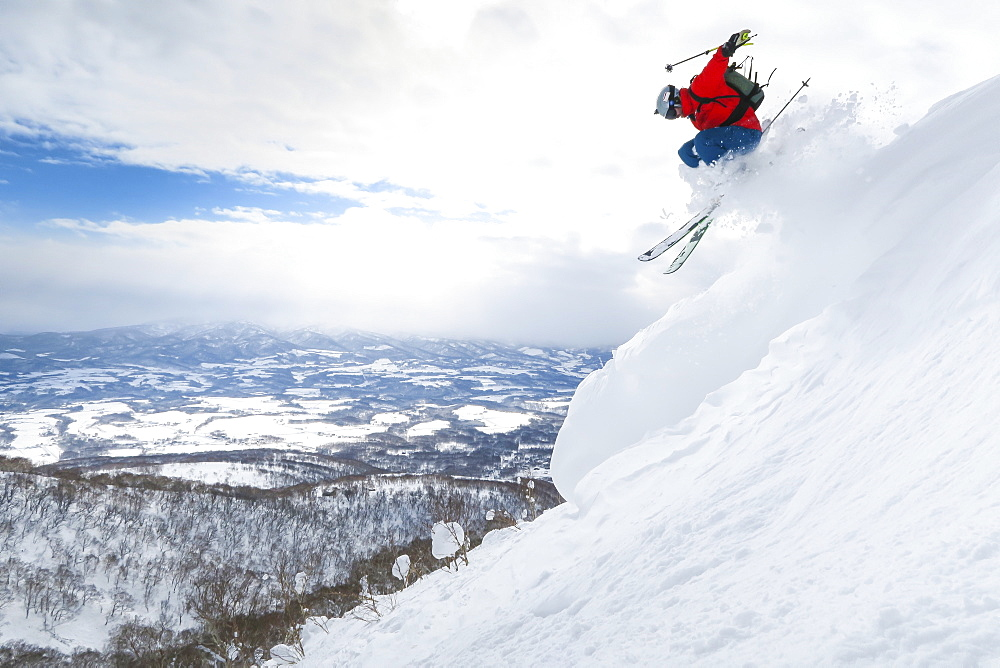 A male skier is jumping in the air onto a slope with deep powder snow in the ski resort Niseko United on the Japanese island of Hokkaido.