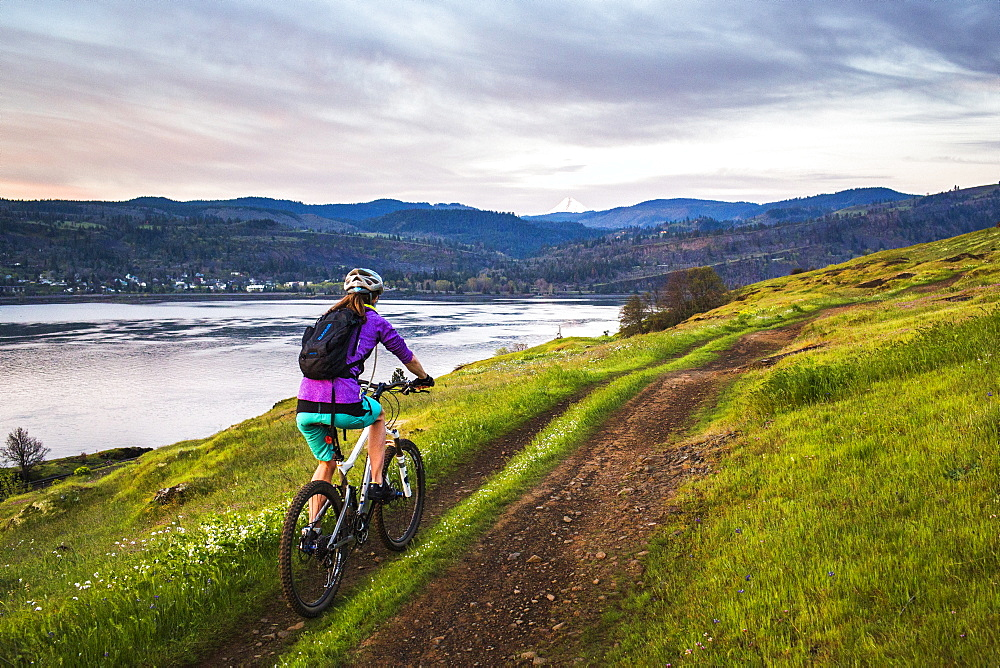 A young woman rides a mountain bike up a single-track trail through an open meadow under early morning sky with river in distance.