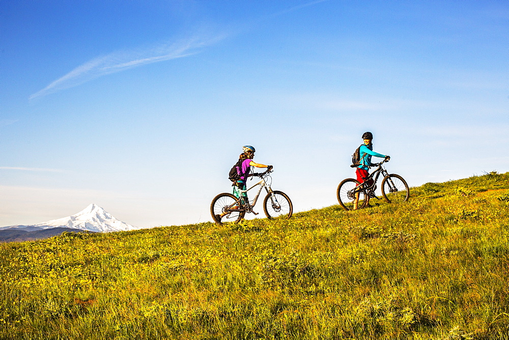Two young women push mountain bikes up a single-track trail through an open meadow.