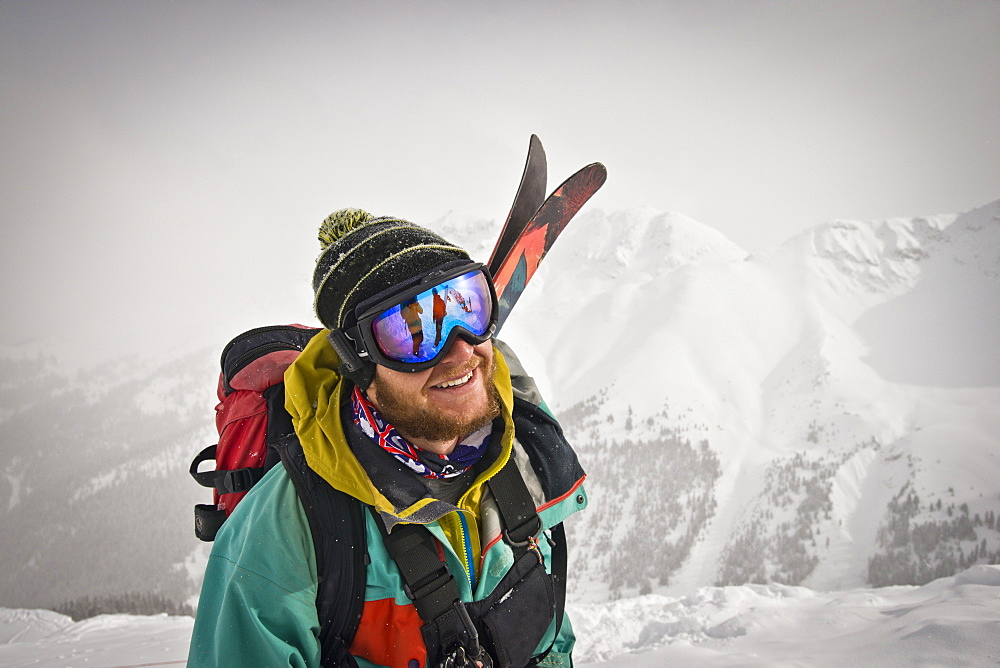 Portrait of a smiling skier on top of a snow covered mountain in Colorado.