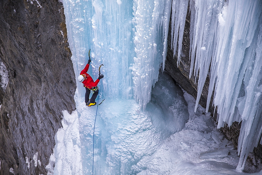 A man in a red jacket is climbing on ice.