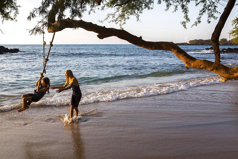 Children play with a rope swing on Waialea beach on the Big Island of Hawaii.
