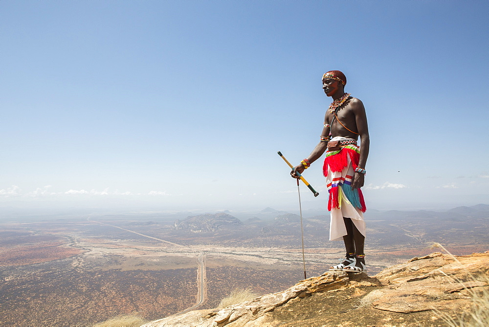 A Samburu warrior stands at the top of Mount Ololokwe in Samburu, Kenya.
