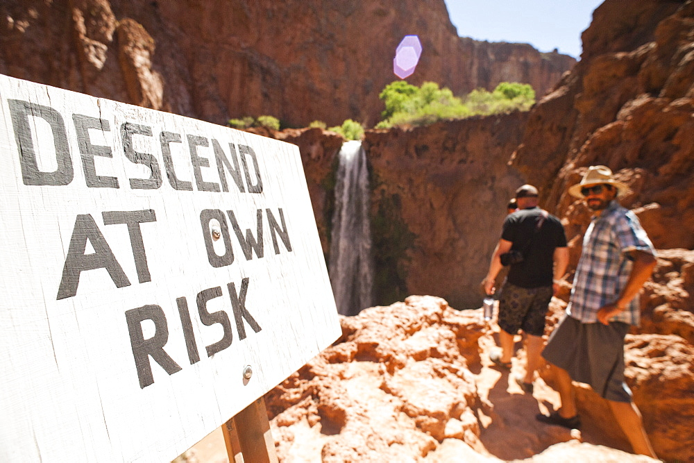 "Two hikers walk by a sign reading ""descend at own risk"" in front of Mooney Falls in the Grand Canyon."