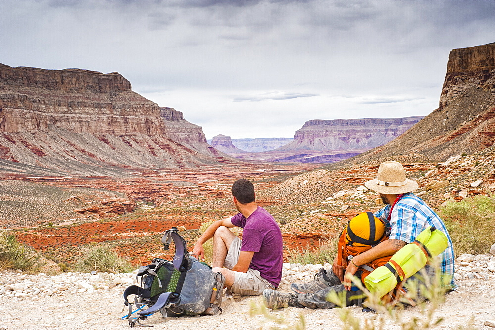 Two backpackers stare out into the Grand Canyon.