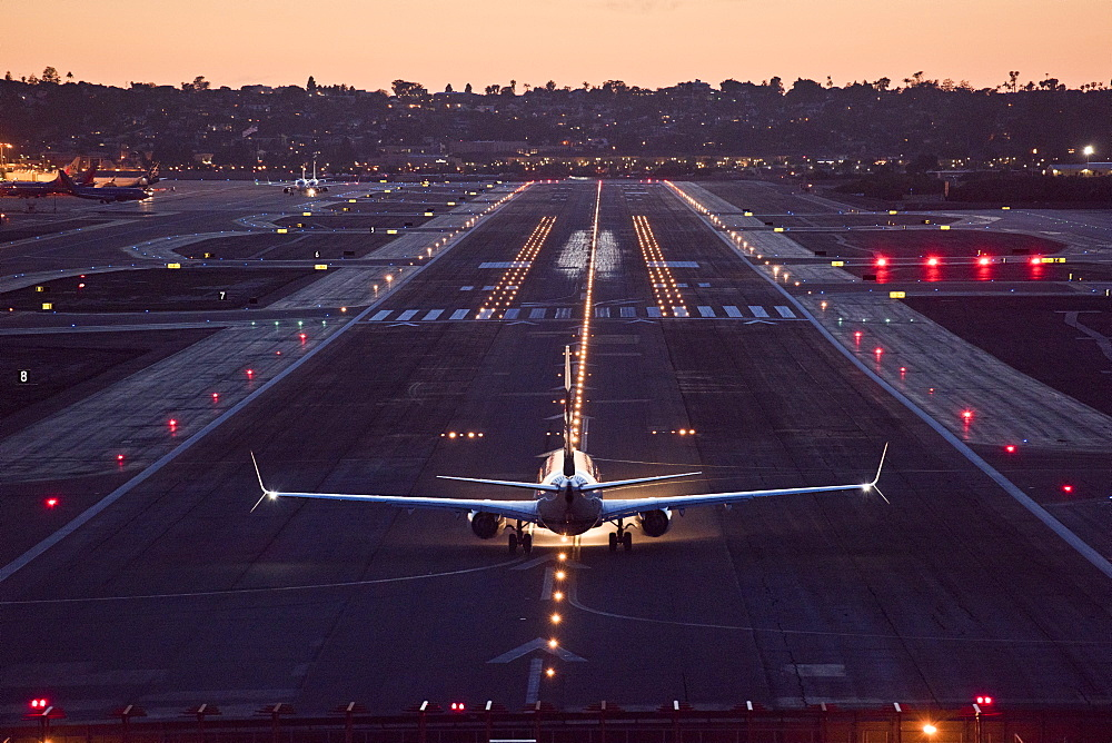 A plane prepares for take off at sunset in San Diego, California.