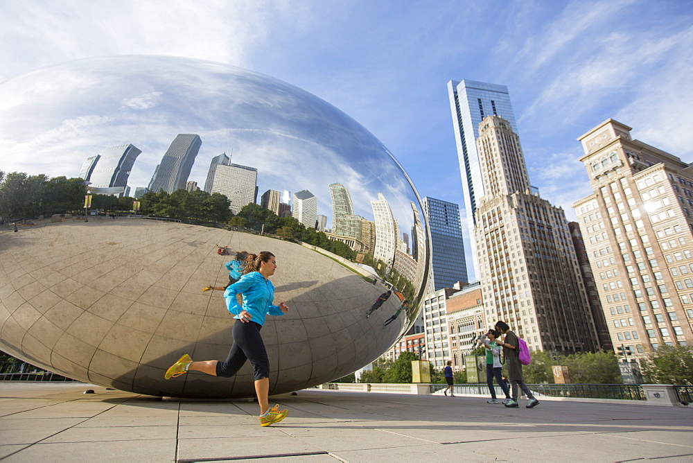 An adult woman running past the Cloud Gate sculpture in Millenium Park. Chicago, Illinois.