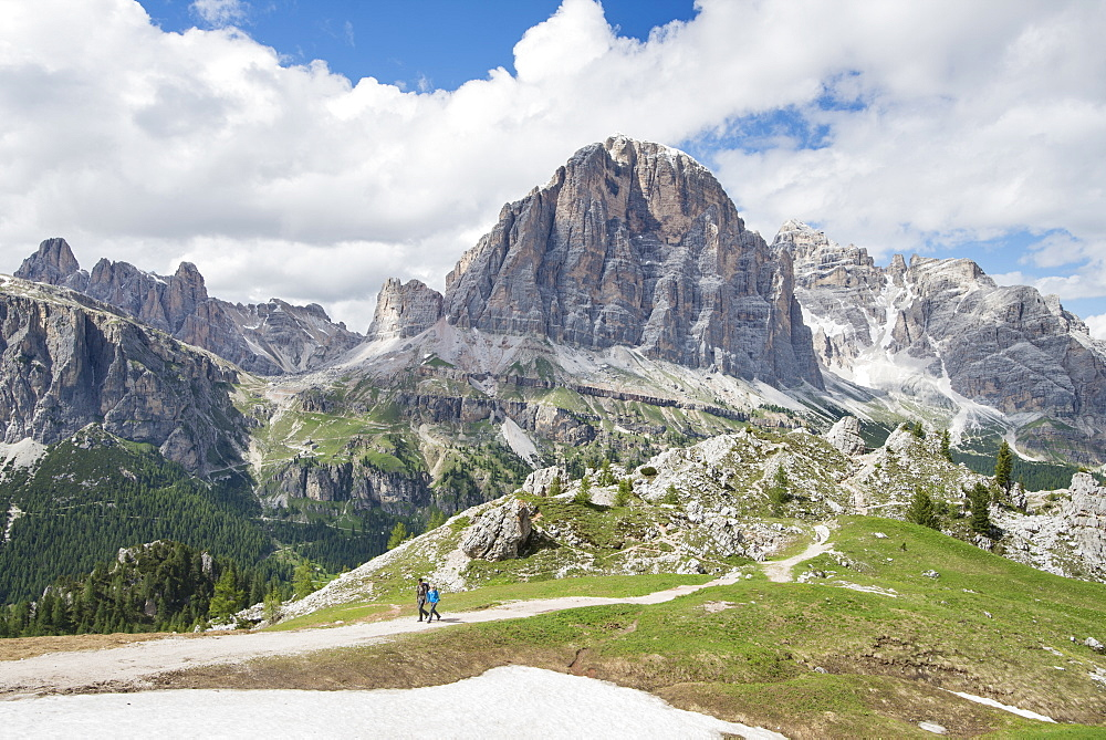 Long Exposure Of Couple Hiking At Cinque Torri Area In Dolomites, Italy