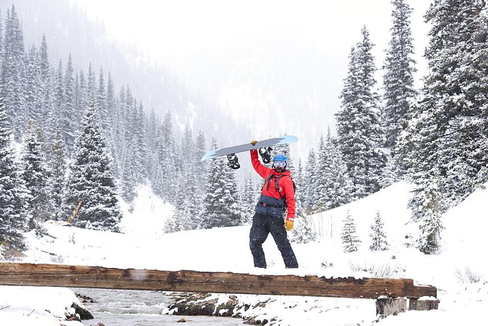 A Snowboarder Holding Board As He Walks Across A Footbridge
