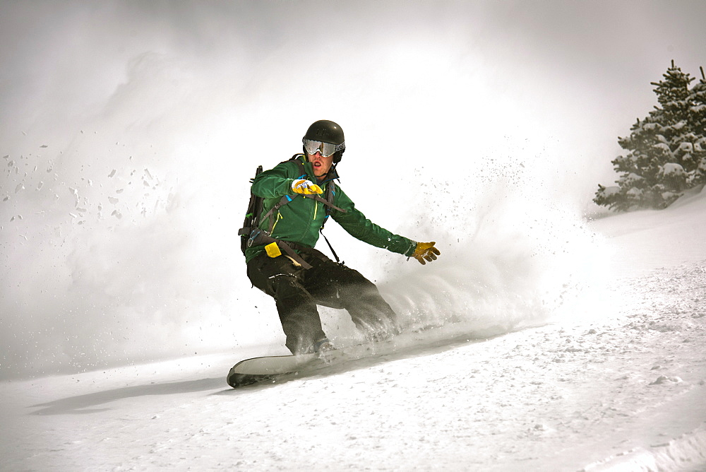 Male Snowboarder Riding In Snow Of Silverton Mountain, Colorado