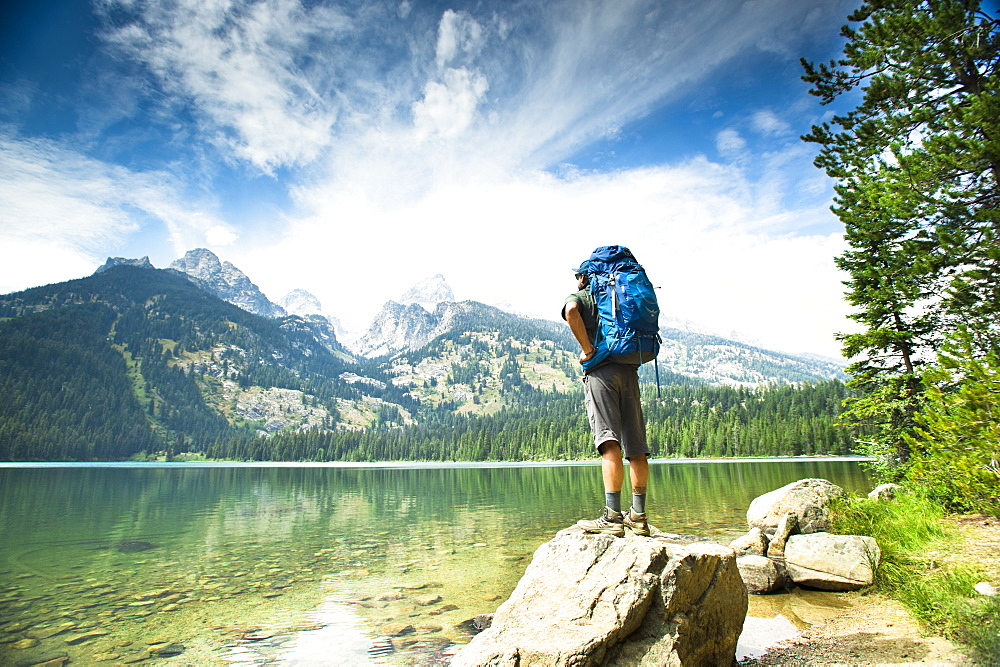 Rear View Of A Backpacker Standing On Rock At A Lake Of The Grand Teton Mountains In Jackson Hole, Wyoming