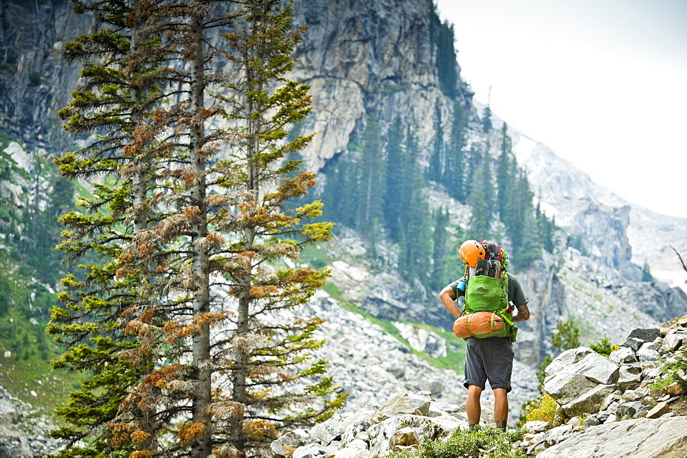 Rear View Of A Backpacker Looking At A View Of The Teton Mountains In Jackson Hole, Wyoming