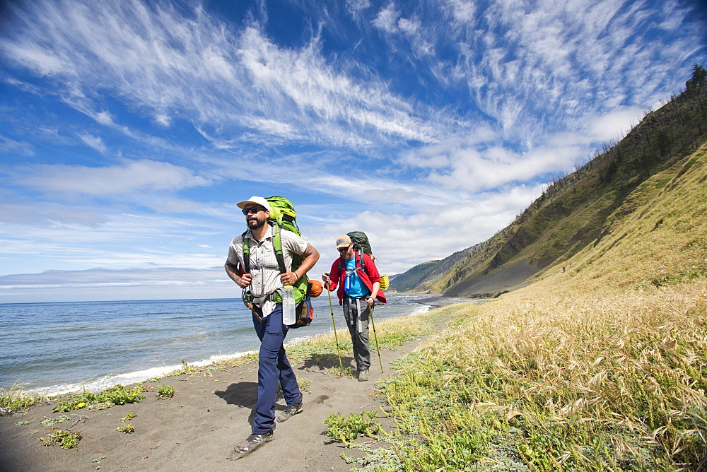 Two backpacker hiking in sandy shoreline of the Lost Coast