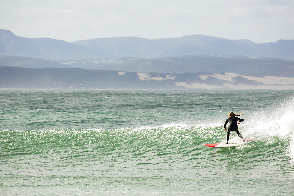 A talented girl surfing at Jefferys Bay, South Africa