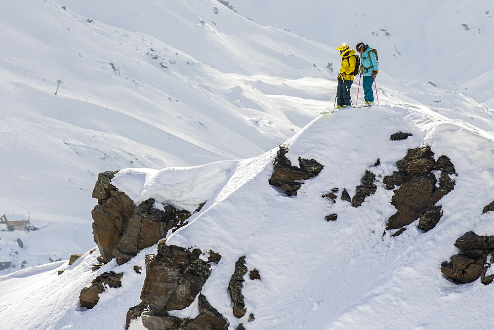 Two Skiers Talking About Their Line Before Dropping In The Face
