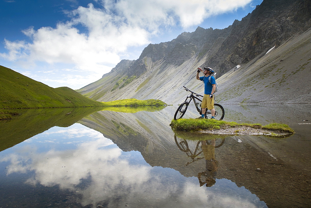 A Mountain Biker Is Drinking Water While Standing At A Beautiful Mountain Lake