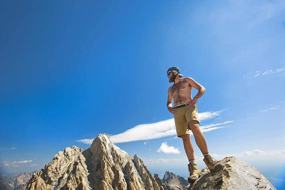 Shirtless Male Hiker Stands On Top Of The Teton Mountains In Grand Teton National Park