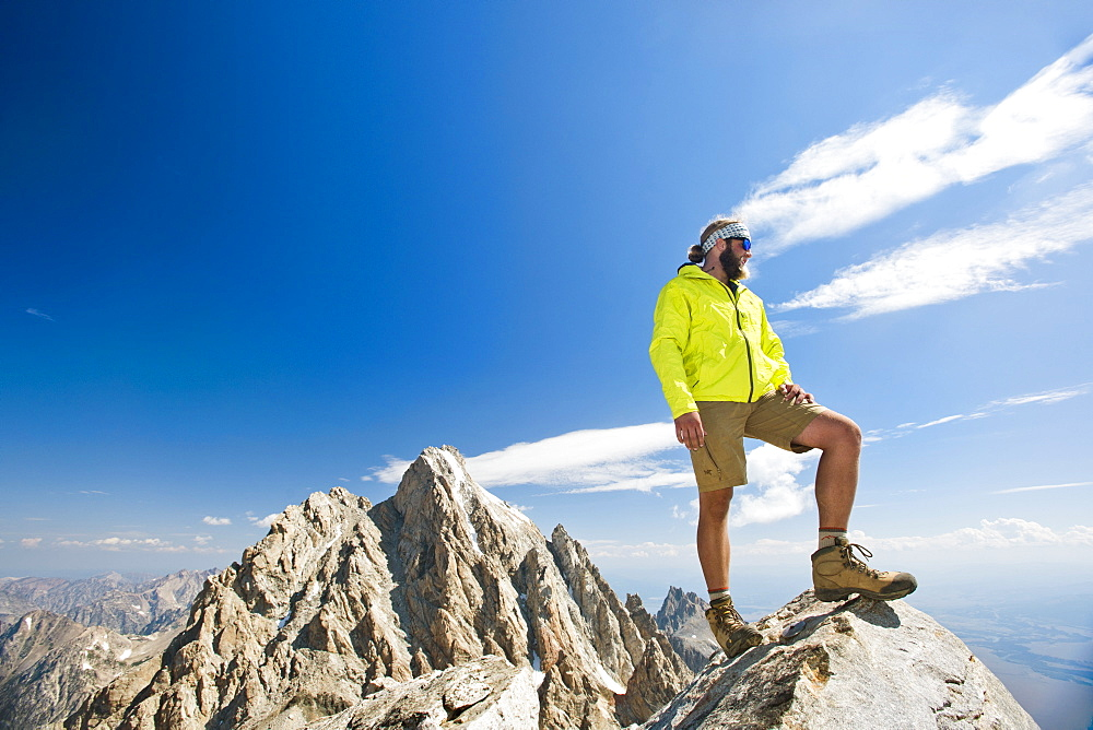 A Hiker Stands On Top Of The Teton Mountains In Grand Teton National Park, Wyoming.