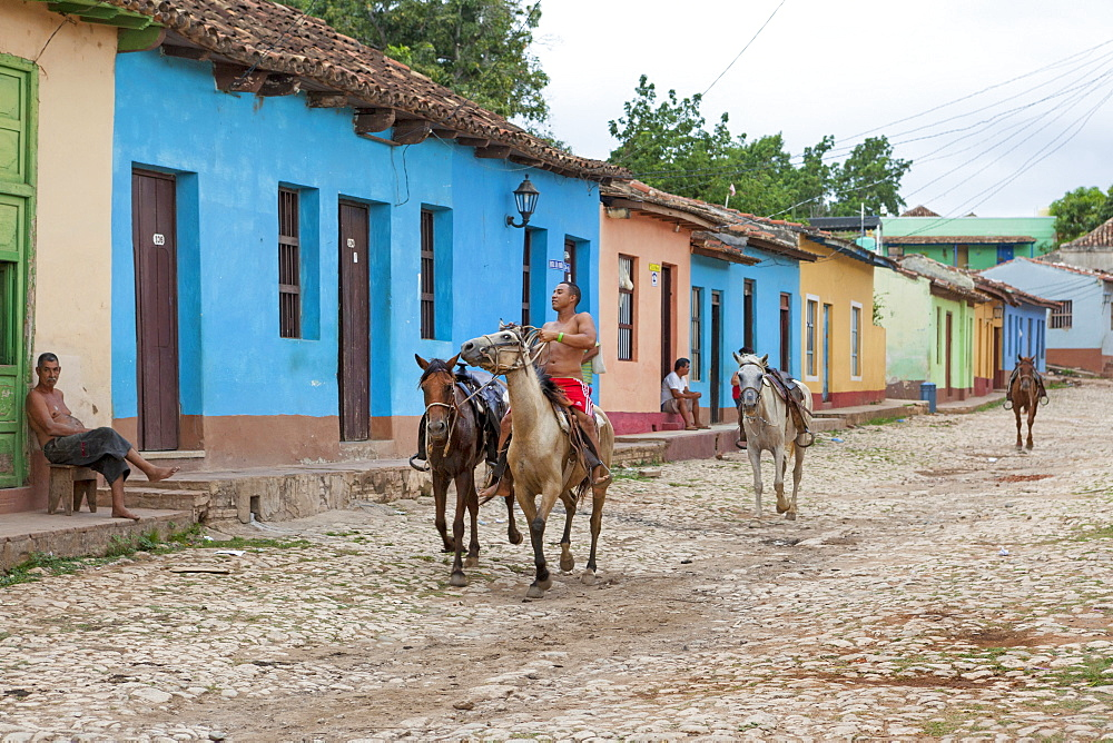 Local Cuban People Riding Horses In The Streets Of Trinidad, Cuba