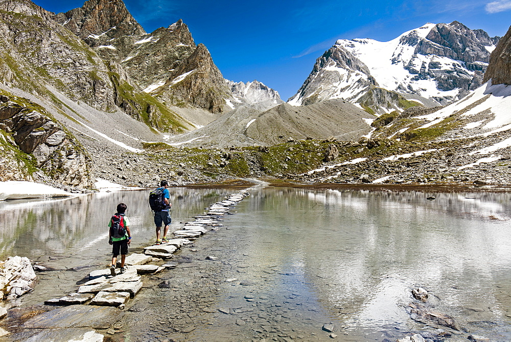 A Man And A Child With Backpack Walking Across A Stone Crossway On Lac Des Vaches