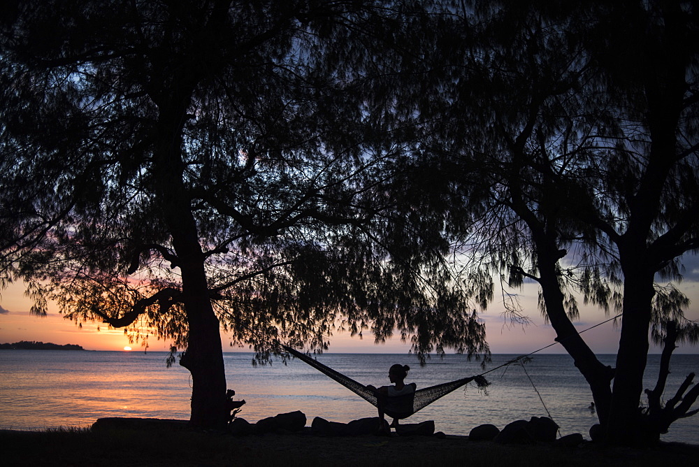 Silhouette Of Young Woman Sitting On Hammock In Gili Air During Sunset In Indonesia