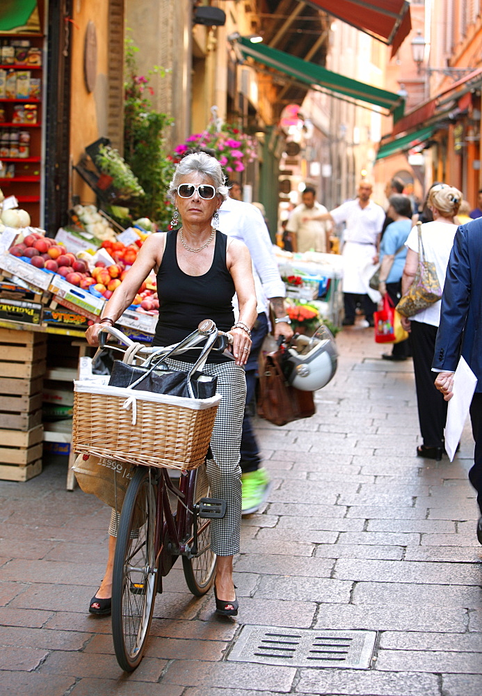 Woman Riding Her Bicycle Through A Local Market In Lessona, Piedmont, Italy