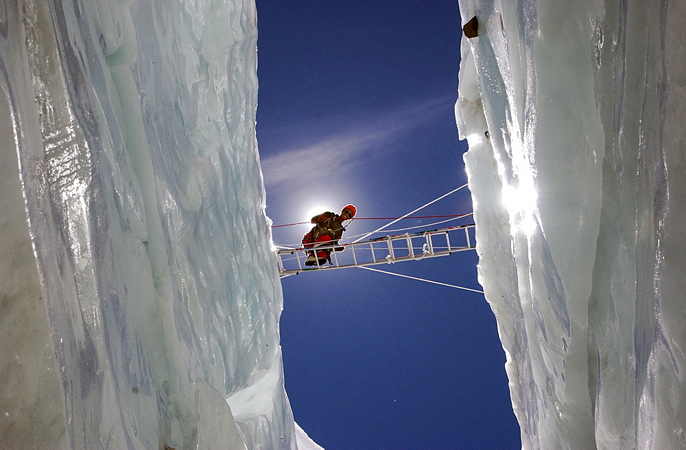 Ngawang Sherpa crosses a massive crevasse on a ladder