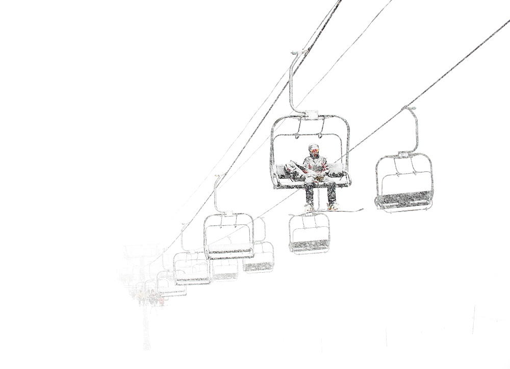 A Lone Ski Patroller Sitting On A Ski Lift In White Out Conditions At Arapahoe Basin Ski Resort
