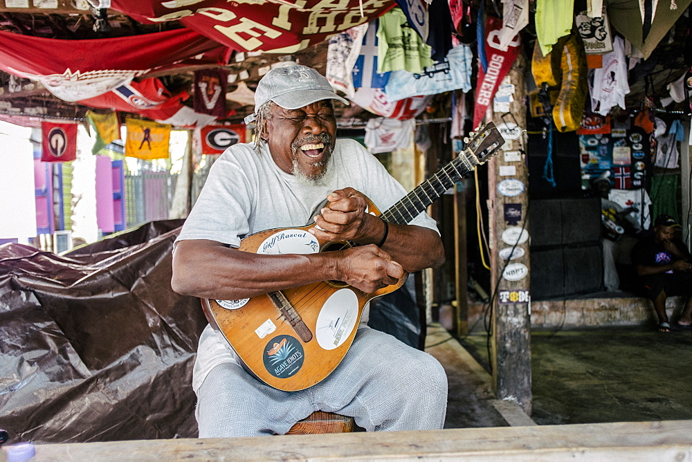 Portrait Of Smiling Man With Guitar Sitting In The Island Of Jost Van Dyke, British Virgin Islands