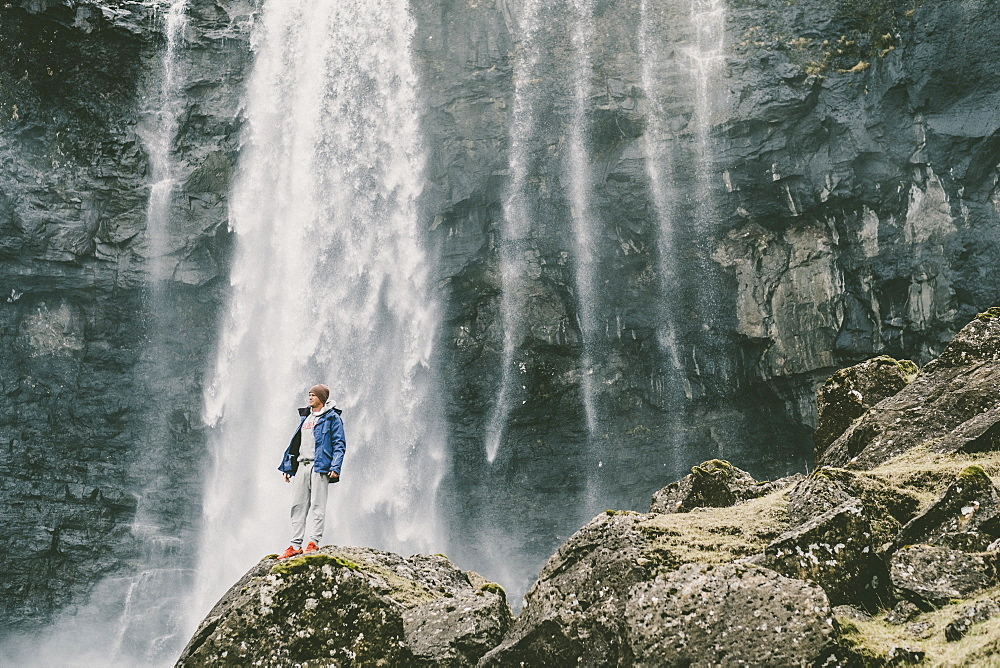 A Man Stands On Rock Besides A Waterfall In The Faroe Islands
