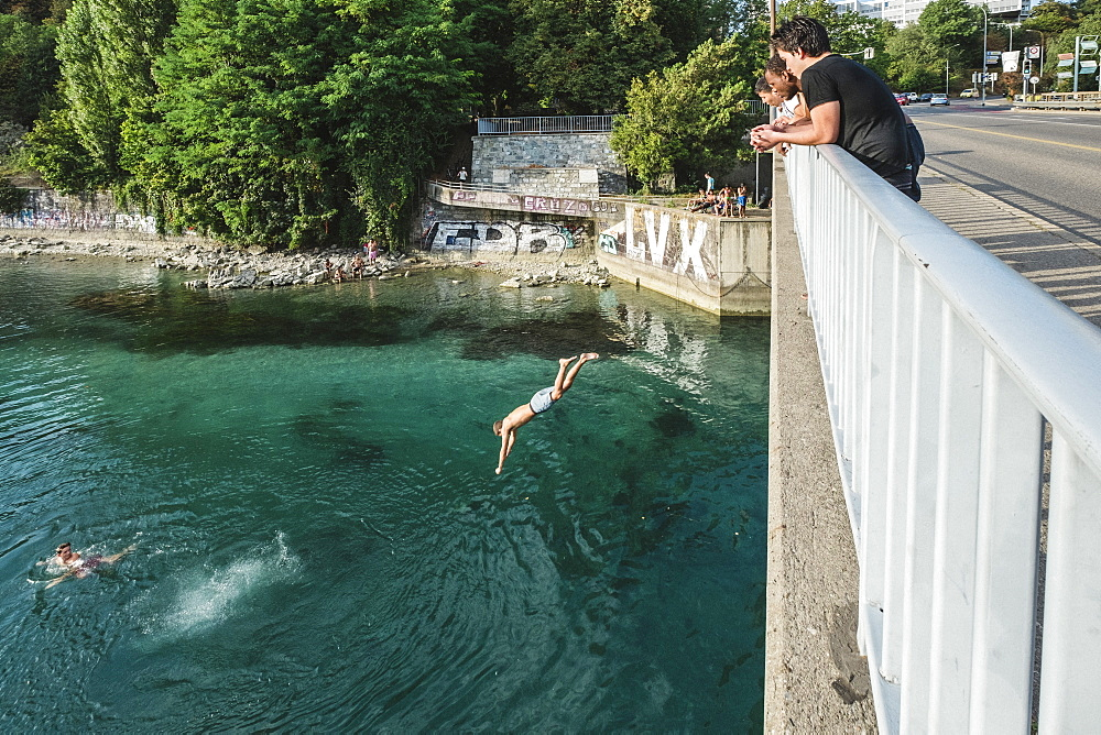 Man Jumping Off A Bridge Into The Rhone River In Geneva, Switzerland