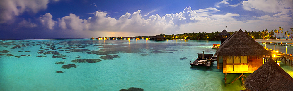 Panoramic view of over water villas under the moonlight at Gili Lankanfushi, in the Maldives.