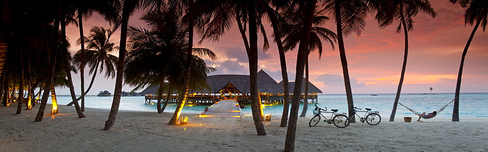 Stilt restaurant in sea behind palm trees at Gili Lankanfushi island at sunset