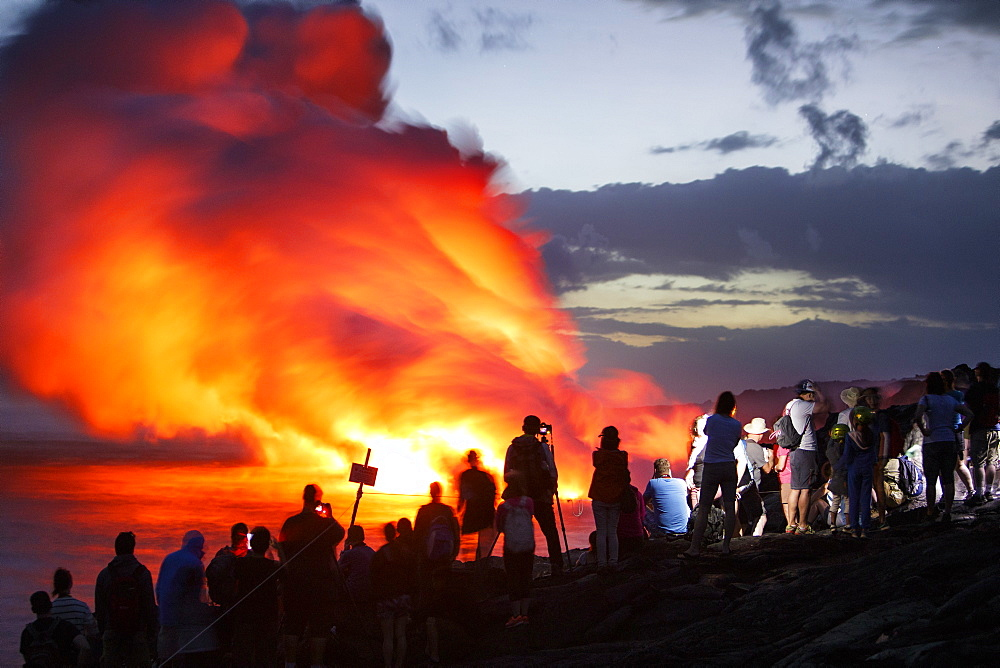 Tourists viewing lava from Kilauea Volcano pouring into ocean at Kamokuna
