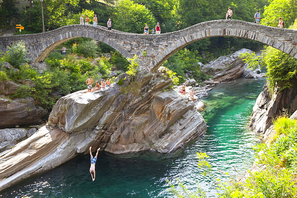 View Of a Diver Leaping From Ponte Dei Salti Bridge Over River At Valle Verzasca, Switzerland
