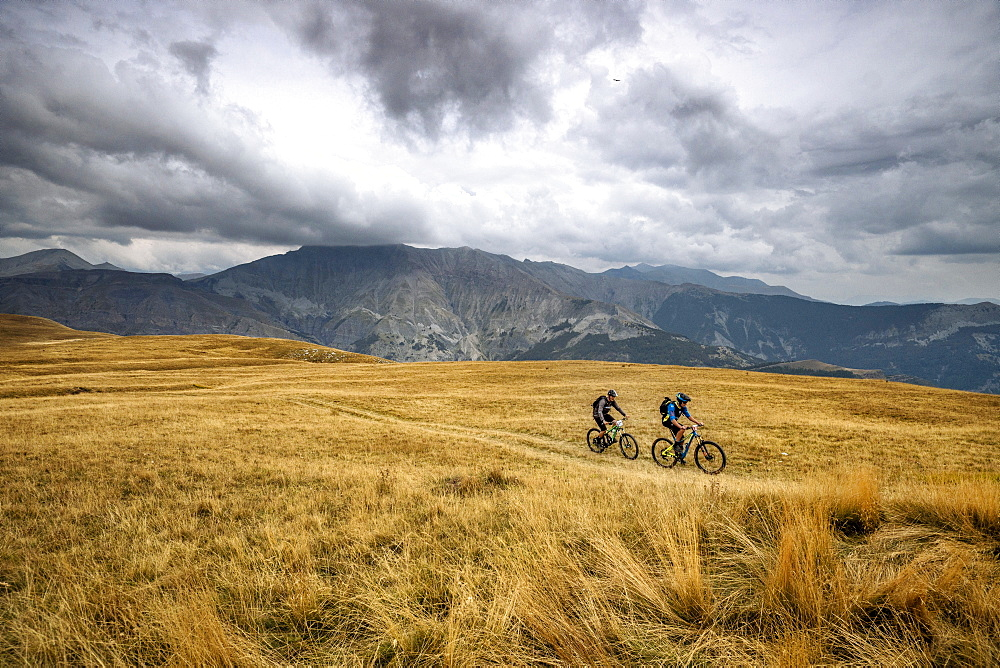 A Pair Of Mountain Bikers Riding On The Mercantour National Park, France