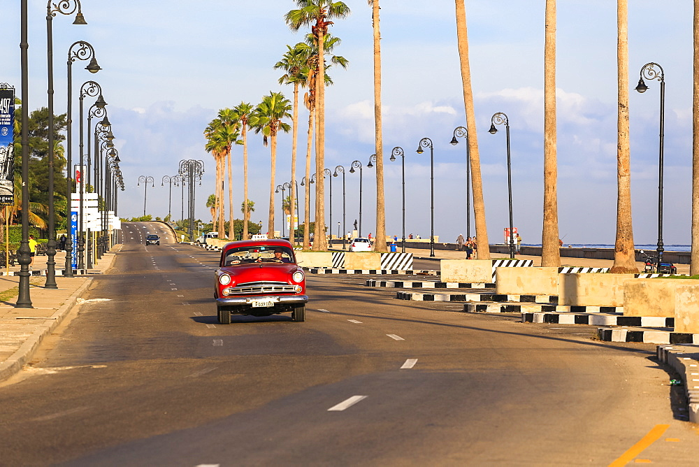 Classic Car Driving Along The Malecon Seawall In Havana's Harbor, Cuba