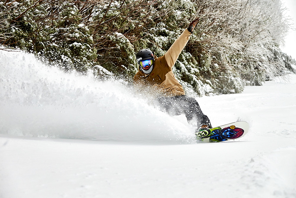 A snowboarder slashing powder inbounds at Sugarbush, VT.
